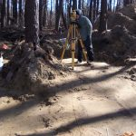 John Potts is using a total station to map the site. Graves can be seen  as grey-ish stains in the soil. (Jill Showell/Edward Otter, Inc.)