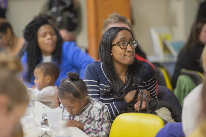 Members of the audience listen to speakers while their children draw pictures during Uneven Play: A Community Dinner and Conversation. (Jonathan Wilson for WHYY)