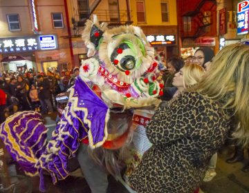 A woman blows a kiss to one of the lions dancing on Race Street during the Chinese New Year celbration. (Jonathan Wilson for WHYY)