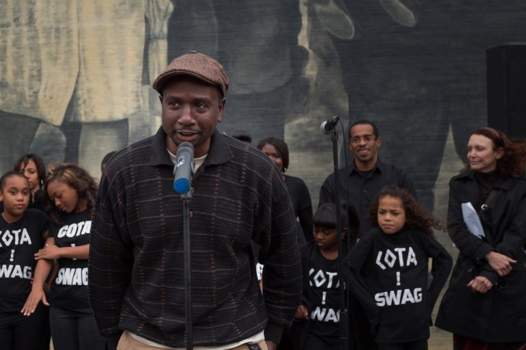 Artist Willis Humphrey. better known as NOMO, speaks at the dedication of his mural,