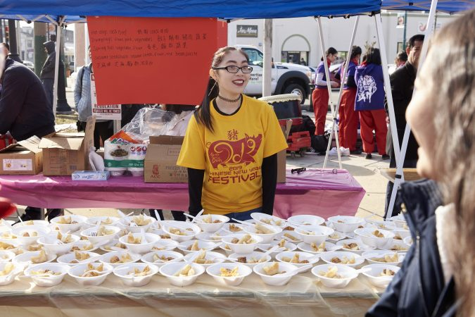 Amy Lee, 21, of Northeast Philadelphia, volunteers at the 2019 Chinese New Year Festival serving cheese wonton and other traditional Chinese foods. (Natalie Piserchio for WHYY)