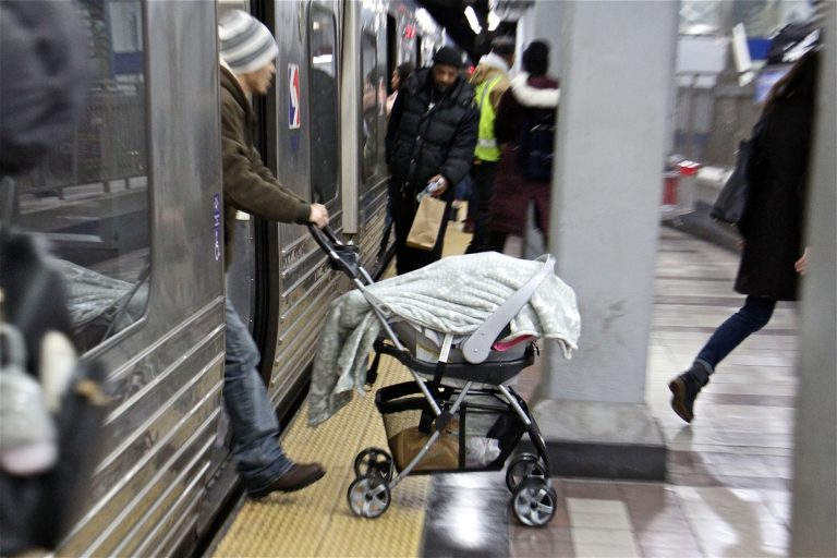 A man pushes a stroller off a SEPTA subway train at the 8th and Market station. (Emma Lee/WHYY)
