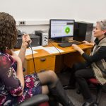 Ann Addis, Temple University clinical instructor and speech pathologist, (right) demonstrates how pitch is measured in the lab. (Kimberly Paynter/WHYY)