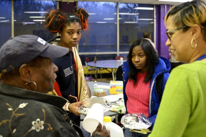 Coach Lurline Jones describes how Lankenau HS ninth-grade La'Kye Powell (2nd from right) acts on the court as members of the girls basketball team from MLK and Lankenau High Schools gather for an end-of-year banquet at the cafeteria of MLK HS, in Northwest Philadelphia, Pa., on February 19, 2019. (Bastiaan Slabbers for WHYY)