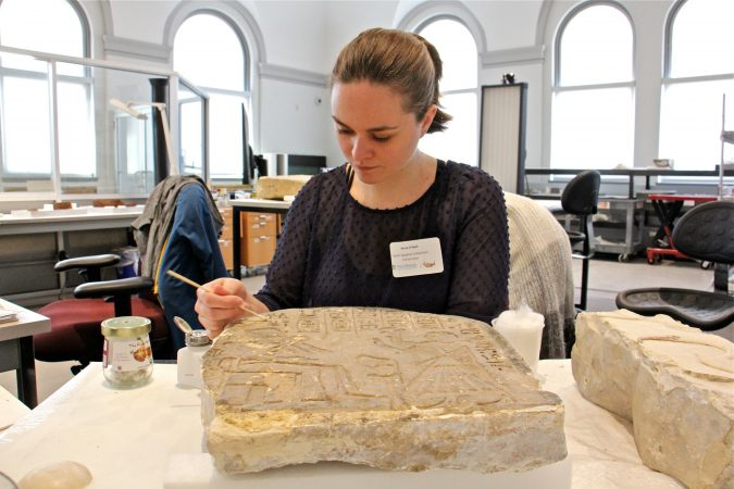 Conservator Anna O'Neill works on a painted limestone stela, or memorial marker, in an open workspace that allows visitors to watch the process and question the conservators. (Emma Lee/WHYY)
