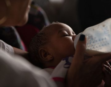 Theresa Reid feeds her five-month-old niece, Ummayyah, a bottle of breast milk that was pumped by Ummayyah's mother, Cierra Jackson, who is serving a 6-to-23-month sentence at Riverside Correctional Facility, in Philadelphia. (Kriston Jae Bethel/Next City)