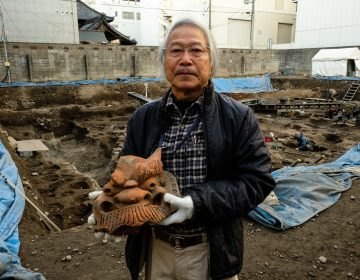 Archaeologist Koji Iesaki holds a carved roof ornament excavated at the former site of the Jyokyo-ji temple in Kyoto. Iesaki and other archaeologists have their hands full, as a pre-Olympic building boom has helped reveal centuries-old artifacts from the city's long history. (Anthony Kuhn/NPR)