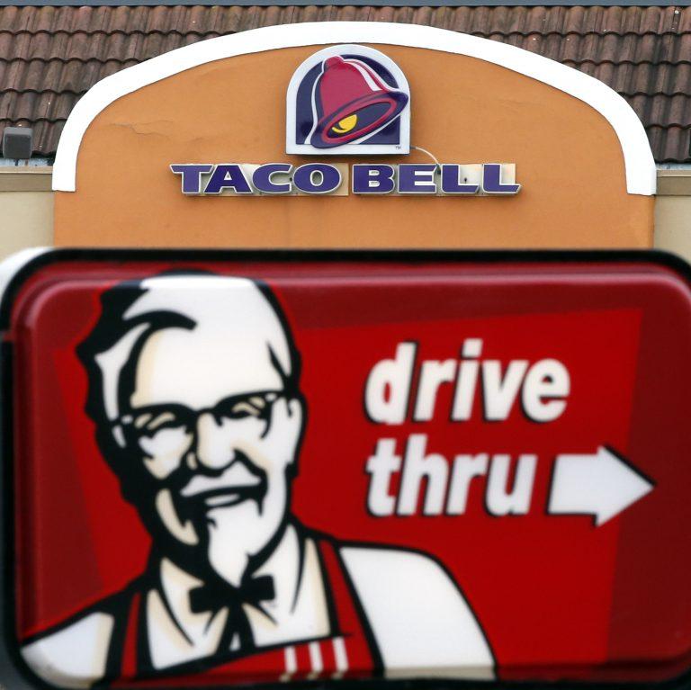 This Jan. 31, 2014, file photo, shows a Taco Bell facade behind a KFC drive-thru sign (Elise Amendola/AP Photo, File)