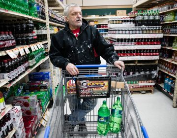 In this March 16, 2017 photo, customer Fran Flanagan is interviewed as he shops for soda at the IGA supermarket in the Port Richmond neighborhood of Philadelphia. The city's tax on sweetened drinks remains controversial two years later. (AP Photo/Matt Rourke)