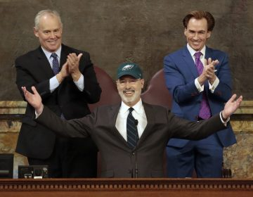 Democratic Gov. Tom Wolf puts on a Philadelphia Eagles hat to celebrate their Super Bowl win before he gives his budget address at the state Capitol in Harrisburg, Pa., on Tuesday, Feb. 6, 2018. (AP Photo/Chris Knight)