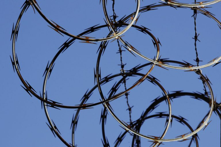 In this Tuesday, Oct. 23, 2018 photo, barbed wire lines the top of a wall at the deactivated House of Correction in Philadelphia. Earlier in 2018, the city announced plans to close the facility amid a decline in the jail population for the city. (Matt Rourke / The Associated Press)