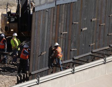 In this Tuesday, Jan. 22, 2019, photo, workers place sections of metal wall as a new barrier is built along the Texas-Mexico border near downtown El Paso. (AP Photo/Eric Gay)