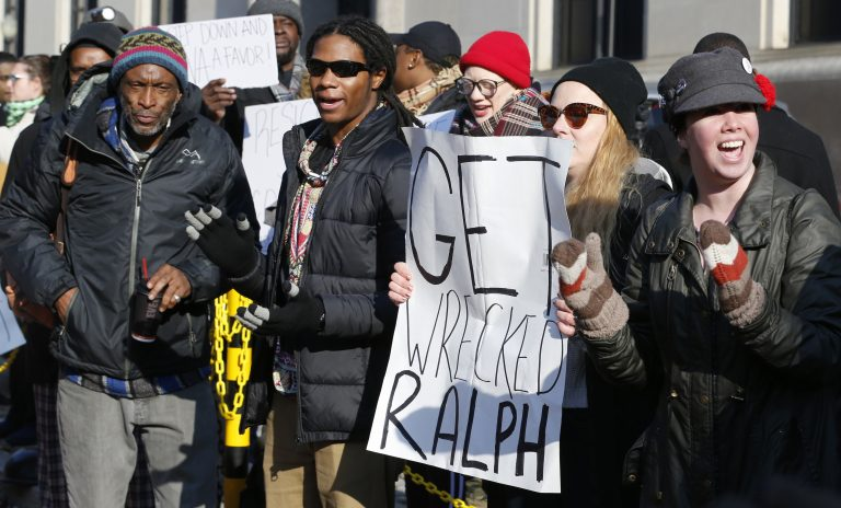Demonstrators hold signs and chant outside the Governors office at the Capitol in Richmond, Va., Saturday, Feb. 2, 2019. The demonstrators are calling for the resignation of Virginia Governor Ralph Northam after a 30 year old photo of him on his medical school yearbook photo was widely distributed Friday. (Steve Helber/AP Photo)