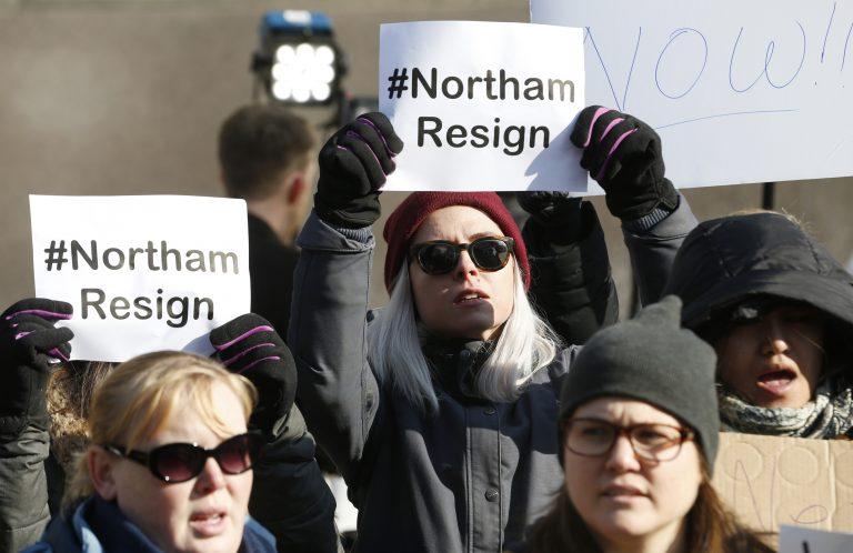 Demonstrators hold signs and chant outside the Governors Mansion at the Capitol in Richmond, Virginia, Saturday, calling for Gov. Ralph Northam to resign. (AP Photo/Steve Helber)