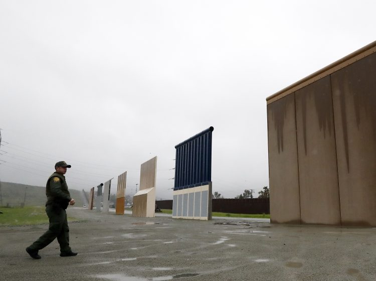 Border Patrol agent Vincent Pirro walks towards prototypes for a border wall Tuesday, Feb. 5, 2019, in San Diego. President Donald Trump is expected to speak about funding for a wall along the U.S.-Mexico border during his State of the Union address Tuesday. (Gregory Bull/AP Photo)