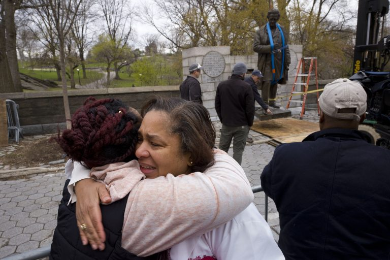 In this Tuesday, April 17, 2018, file photo, Dr. Bernadith Russell hugs a friend as the statue of Dr. J. Marion Sims, is removed from New York's Central Park. (Mark Lennihan/AP Photo, File)