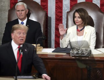 Speaker of the House Nancy Pelosi, D-Calif., raises her hand in a gesture to quiet the Democrats as President Donald Trump delivers his State of the Union address to a joint session of Congress on Capitol Hill in Washington, as Vice President Mike Pence watches, Tuesday, Feb. 5, 2019. (Andrew Harnik/AP Photo)