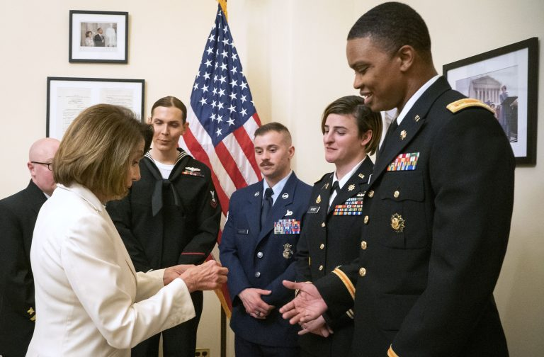 In this Tuesday, Feb. 5, 2019 photo released by her office, Speaker of the House Nancy Pelosi, D-Calif., left, gives challenge coins to U.S. Army Maj. Ian Brown, right, and other military service members to thank them for their service, in her office at the Capitol following the State of the Union address in Washington. Brown, 38, is a two-time Bronze Star recipient who transitioned from female to male while advising the Army's deputy chief of staff in operations and planning. (Julio Obscura/Office of the Speaker of the House Nancy Pelosi via AP)