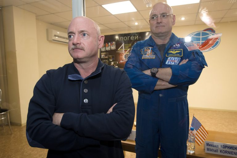 In this March 26, 2015 file photo, U.S. astronaut Scott Kelly, (right), crew member of the mission to the International Space Station, stands behind glass in a quarantine room, behind his brother, Mark Kelly, also an astronaut, after a news conference in the Russian-leased Baikonur, Kazakhstan cosmodrome. Nearly a year in space put Scott Kelly's immune system on high alert and changed the activity of some of his genes compared to his Earth-bound identical twin, according to a report released on Friday, Feb. 15, 2019. (Dmitry Lovetsky/AP Photo)