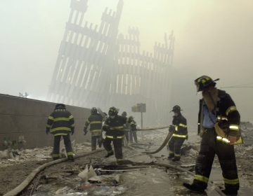 In this Sept. 11, 2001 file photo, with the skeleton of the World Trade Center twin towers in the background, New York City firefighters work amid debris on Cortlandt St. after the terrorist attacks. On Friday, Feb. 15, 2019, Rupa Bhattacharyya, the September 11th Victim Compensation Fund special master, announced that the compensation fund for victims of the Sept. 11, 2001 terror attacks will cut future payments by 50 to 70 percent because the fund is running out of money. (Mark Lennihan/AP Photo, File)