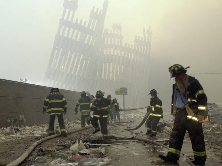 In this Sept. 11, 2001 file photo, with the skeleton of the World Trade Center twin towers in the background, New York City firefighters work amid debris on Cortlandt St. after the terrorist attacks.  (Mark Lennihan/AP Photo, File)
