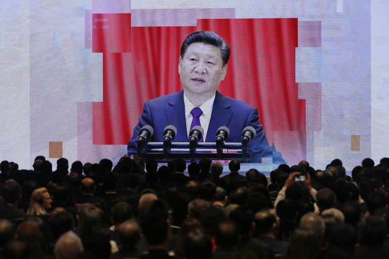 A screen shows Chinese President Xi Jinping during a symposium on the