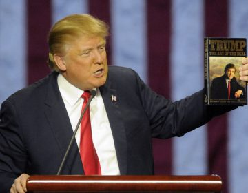 In this file photo, then-Republican presidential candidate Donald Trump holds up his book 'The Art of the Deal', given to him by a fan as he speaks during a campaign stop Saturday, Nov. 21, 2015 in Birmingham, Ala. (Eric Schultz/AP Photo)