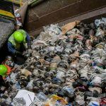 Waste Management technicians clear plastic bags and plastic sheeting from a recycling center screen. Plastic bags and sheeting are a major challenge for recyclers, as they snarl sorting equipment, cause contamination, and drive up processing costs.
