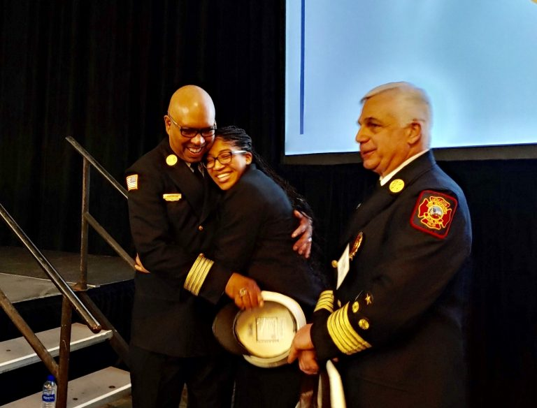 Ardavia Lee, daughter of a fallen Wilmington firefighter, is embraced by members of the fire department after receiving a $25,000 scholarship. (Zoe Read/WHYY)
