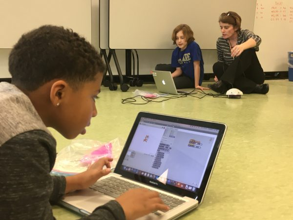 Teacher Laurie Drumm helps students program their robot to navigate a maze. (Mark Eichmann/WHYY)
