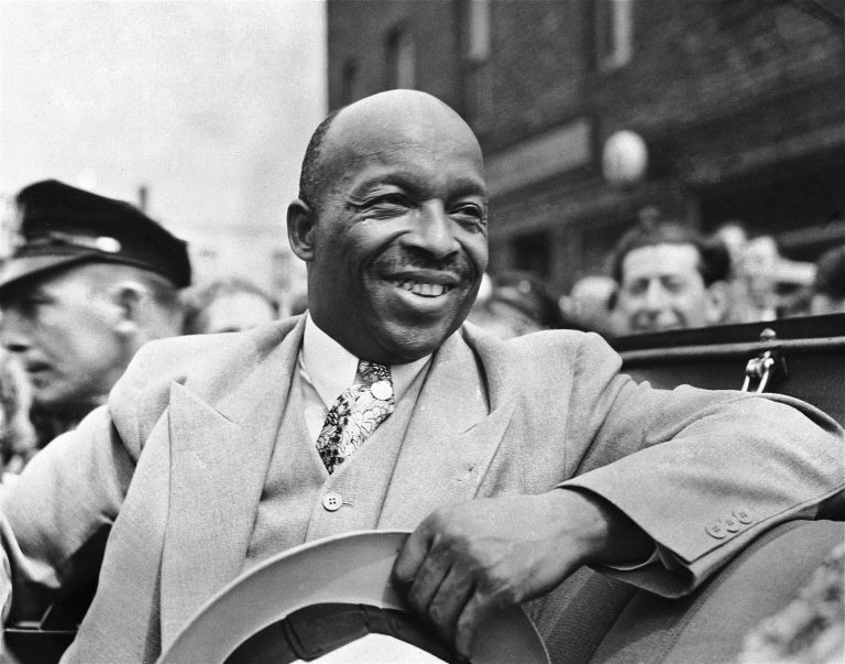 American-African spiritual leader Father Divine smiles as he leads a parade of his followers from Harlem to the docks in New York, on Aug. 20, 1936, to board the paddle-steamer City of Kennsburg to take them on the first stage of their great trek to their new camp in Ulster County, New York State. (AP Photo)