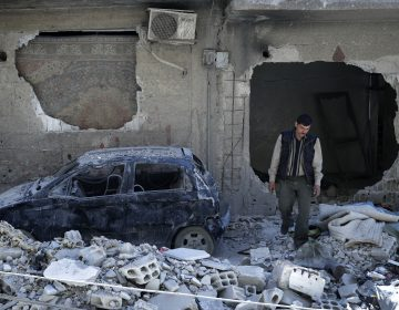 A man walks amid rubble in the Syrian town of Douma in April 2018. A report out Sunday confirmed that a chemical attack early that month was one of hundreds since the start of the Syrian civil war. (Hassan Ammar/AP Photo)