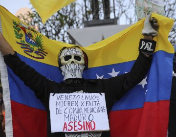 An anti-government protester on Saturday in Caracas wears a sign that reads,