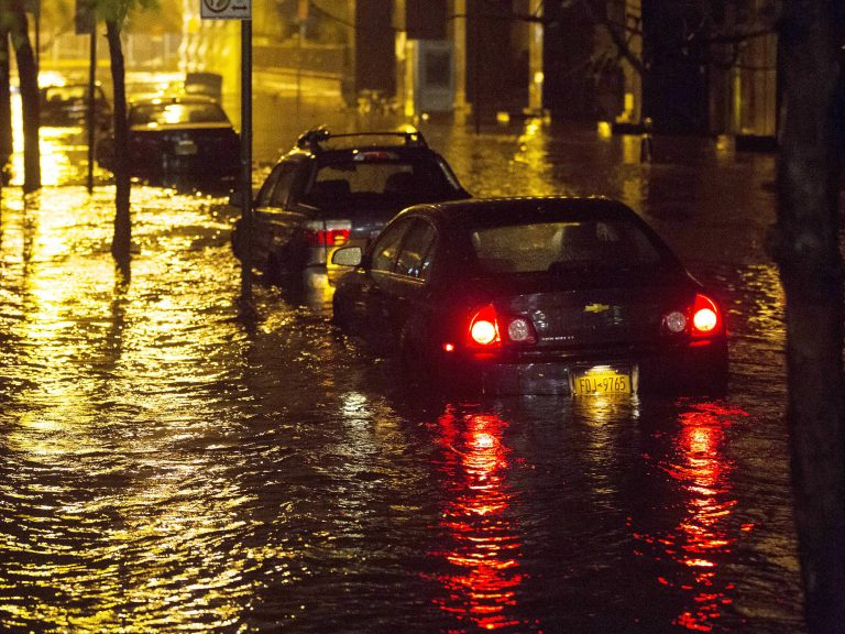 Vehicles sit in high floodwater during a storm surge associated with Superstorm Sandy in 2012, near the Brooklyn Battery Tunnel in New York. (John Minchillo/AP)