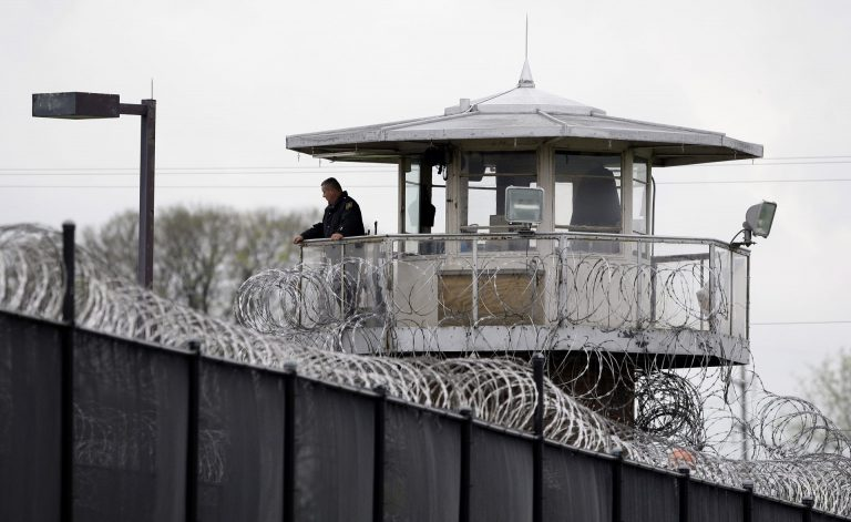A solitary corrections officer looks out from a tower at one corner of the state prison in Camp Hill. (Carolyn Kaster/AP Photo)