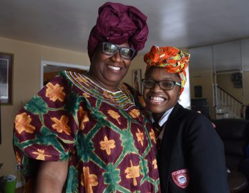 Geniah Miller in her Camden Academy Charter High School uniform and the Nigerian head wrap with her mother, Chioma Sullivan, at their Camden home on Feb. 11, 2019, after Miller was sent home from school. (April Saul for WHYY)