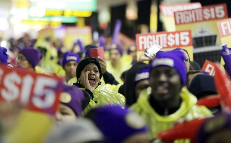 A woman shouts while marching with service workers asking for $15 minimum wage pay during a rally at Newark Liberty International Airport, Tuesday, Nov. 29, 2016, in Newark, N.J. The event was part of the National Day of Action to Fight for $15. The campaign seeks higher hourly wages, including for workers at fast-food restaurants and airports. (Julio Cortez/AP Photo)