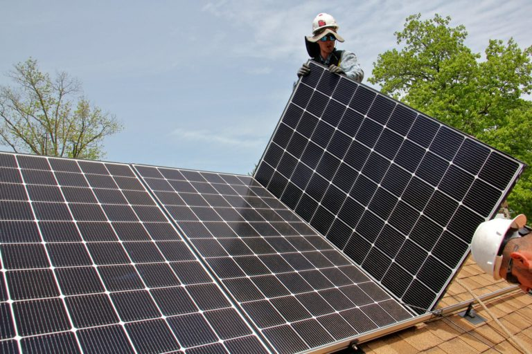 Patrick Whittaker of Solar States installs solar panels on the roof of a home in Bryn Mawr. (Emma Lee/WHYY)