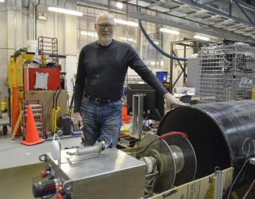 Red Whittaker stands beside an early prototype of RadPiper, a pipe-crawling robot that will help decommission uranium enrichment facilities in Ohio and Kentucky. Whittaker has worked in robotics for four decades at Carnegie Mellon University, and he developed several robots in the 1980s that helped clean up after the Three Mile Island incident. (Amy Sisk/StateImpact Pennsylvania)