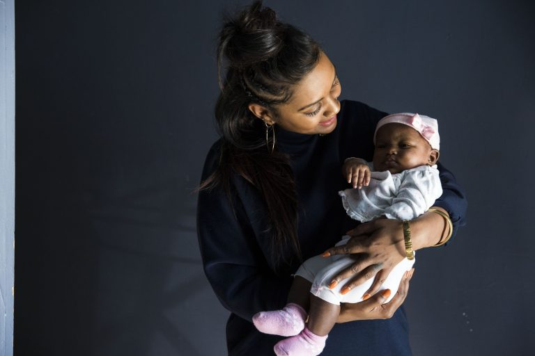 Midwife Asasiya Muhammad poses for a portrait with two-month-old Winter Nimmons at her practice, Inner Circle Midwifery, on February 9. Muhammad delivered Nimmons two months ago and had to resuscitate Winter when she was born not breathing. (Rachel Wisniewski/WHYY)