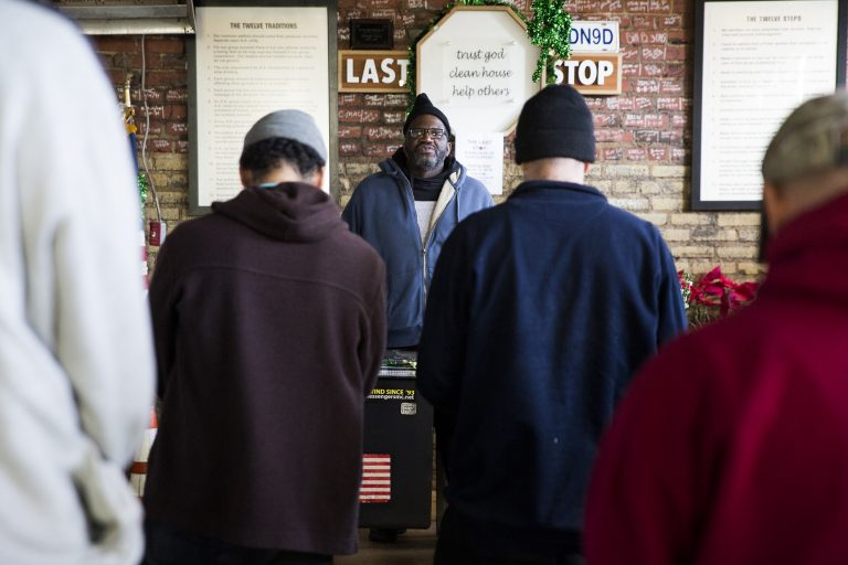 Nathanial McCray (center) leads the morning mediation at the Last Stop recovery center on Feb. 19, 2019. Meditation meetings encourage the center clients to remain mindful and present. McCray was picked to lead the meeting due to the positive example that he's set in his sobriety. A different client in good standing is picked to lead the meeting each morning. (Rachel Wisniewski for WHYY)