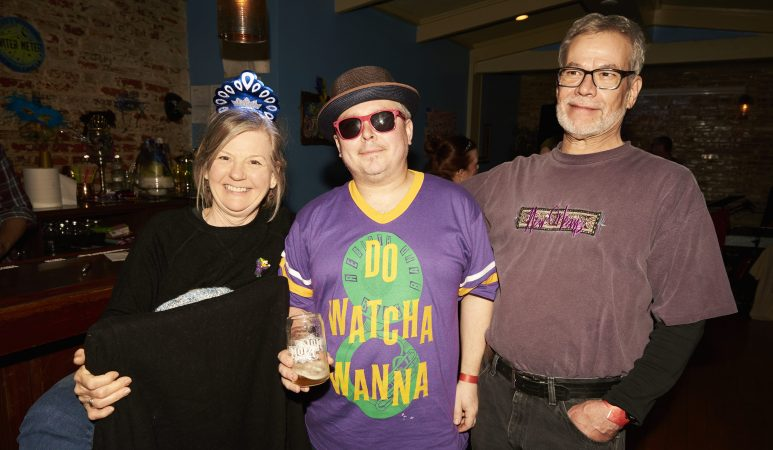New Orleans natives Jan Marvin, Chris Marsceill, and Jeff Marvin celebrate Mardi Gras at the Acadia Bar in South Philadelphia. (Natalie Piserchio for WHYY)