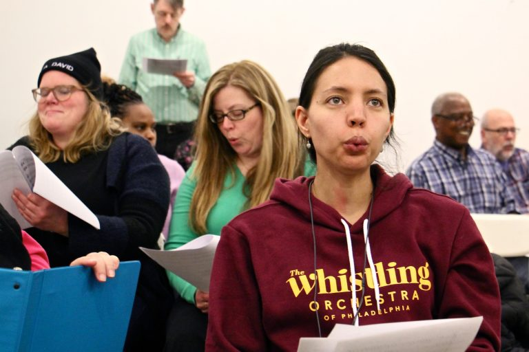 Bria Blauvelt rehearses with the newly formed Whistling Orchestra of Philadelphia. She traveled from her home in Egg Harbor Township for the opportunity to put her talent to work with a group. (Emma Lee/WHYY)