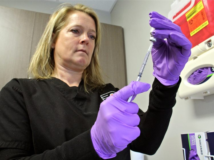 Registered nurse Nicole Rodriguez draws a dose of mumps vaccine at the Temple student health center, where vaccinations are recommended for students who are experiencing symptoms or have been exposed to infected students. (Emma Lee/WHYY)
