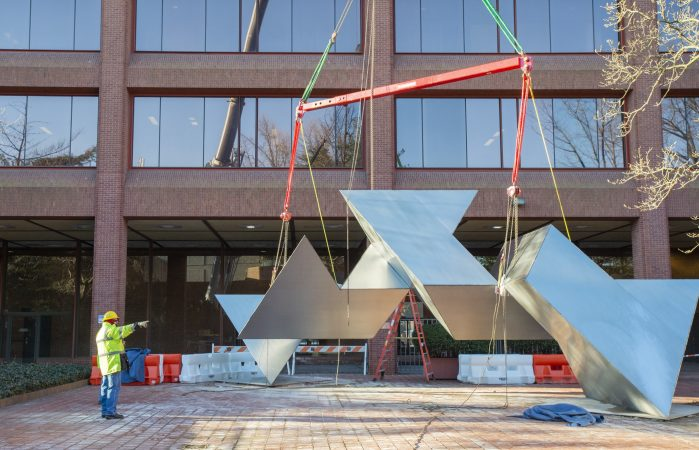 A workman makes final preparations to hoist the Whie Water sculpture. White Water, a sculpture by Philadelphia artist Robinson Fredenthal is moved from the garden behind the Wells Fargo building in Old City to its new home at the Woodmere Art Museum in Chestnut Hill. (Jonathan Wilson for WHYY)