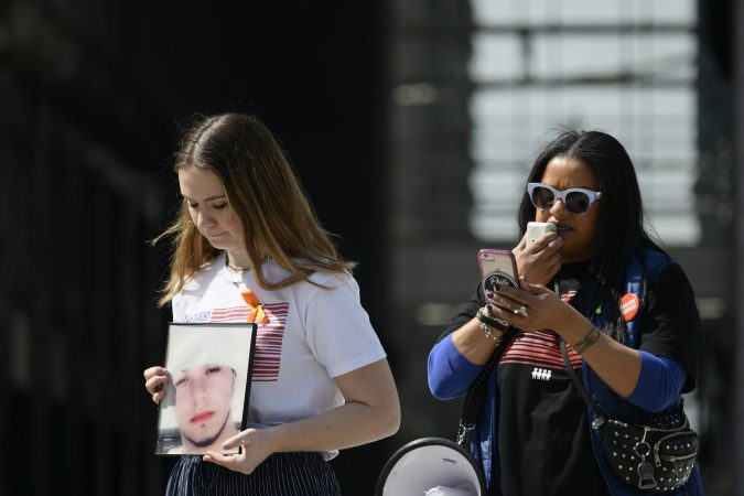 Alex Franzino, 17, March For Our Lives Philadelphia Director of Operations, holds a picture of the nephew of Roz Pichardo, while she reads out names of people killed in Philadelphia, during an anti-gun violence rally at LOVE Park on Sunday. (Bastiaan Slabbers for WHYY)