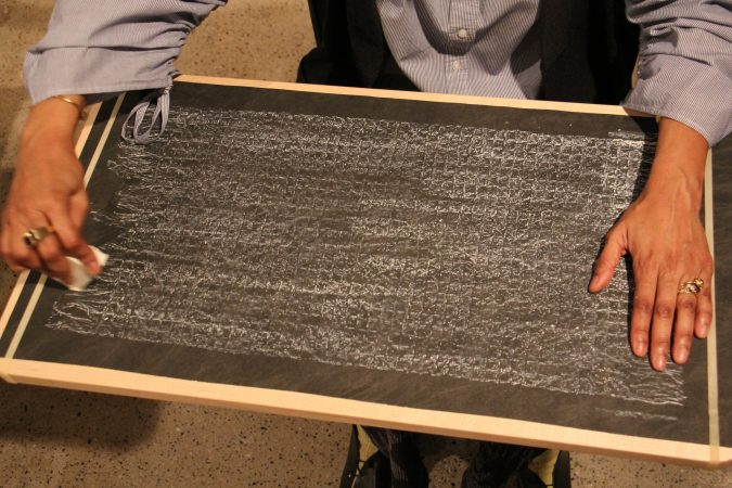 Sonya Clark makes a chalk rubbing of the Confederate truce flag, an activity available to visitors to her exhibit at the Fabric Workshop and Museum. (Emma Lee/WHYY)