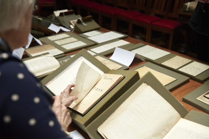 Lynne Farrington, Project Director of Whitman at 200, carefully turns a page in an early edition of Walt Whitman's Leaves of Grass. (Natalie Piserchio for WHYY)