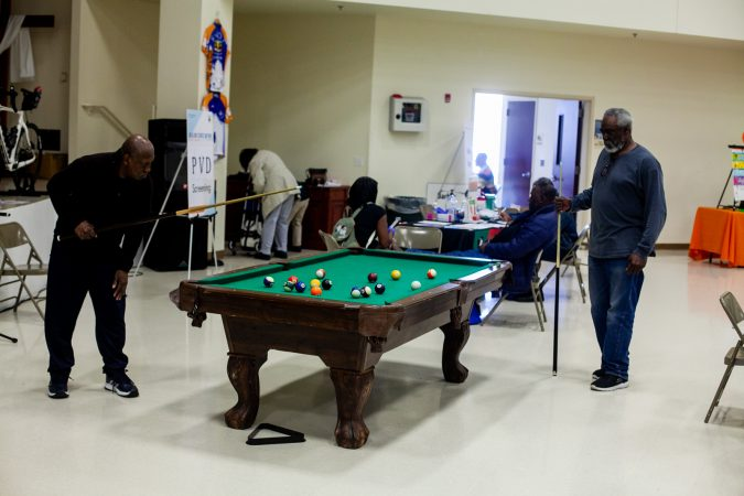 Daniel Brooks, (left), and Tyrone Hicks play a game of pool at the 2019 Men's Health Iniative at Enon Tabernacle Baptist Church Saturday. (Brad Larrison for WHYY)