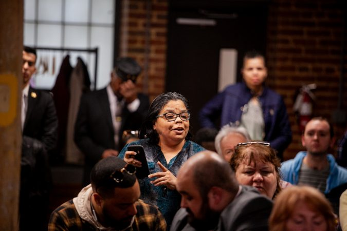 Kensington resident Rosalind Lopez reads statistics off of her phone that she had compiled in opposition to a proposed supervised injection site during a meeting on the city's efforts to combat the opioid epidemic. (Brad Larrison for WHYY)